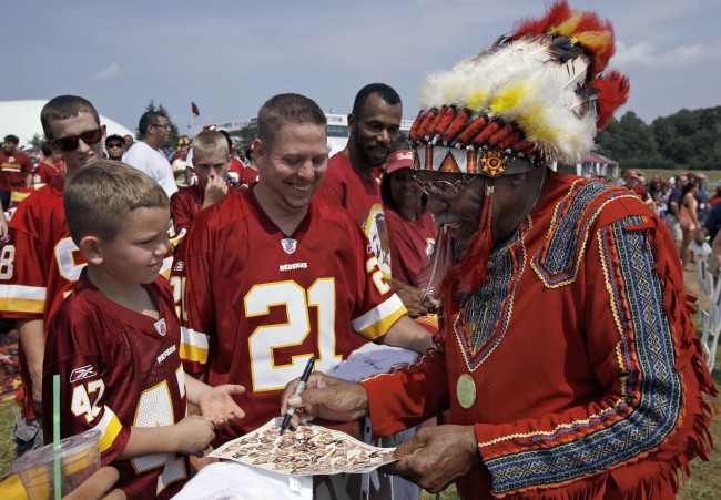 "- In this Saturday, Aug. 4, 2012 file photo, Zena ""Chief Z"" Williams signs autographs during fan appreciation day at the Washington Redskins' NFL football training camp at Redskins Park in Ashburn, Va. President Barack Obama says that if he owned the Washington Redskins, he would ""think about changing"" the team name, wading into the controversy over a football nickname that many people deem offensive to Native Americans. Obama, in an interview on Friday, Oct. 4, 2013, said team names like the Redskins offend ""a sizable group of people."" He said that while fans get attached to the nicknames, nostalgia may not be a good enough reason to keep them in place. (AP Photo/Alex Brandon)"