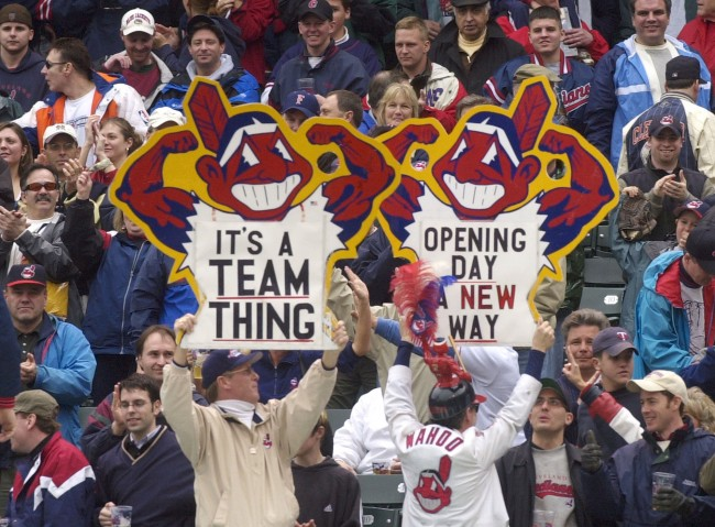 In this April 8, 2002 file photo, fans hold up Chief Wahoo logo signs as they celebrate the Cleveland Indians' opening win over the Minnesota Twins in Cleveland, Ohio. Many experts say using any human being as a mascot is demeaning regardless of the depiction, though communities at times have been reluctant to cede old traditions. The team continues to use the image of Chief Wahoo despite criticism from those who find it offensive.