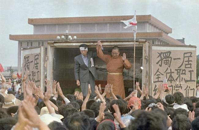 Li Nan, left, of Du Yiju Restaurant, and Yuan Chi, a monk with the China Buddhist Association, receive cheers from students in Tiananmen Square, Sunday, May 21, 1989, Beijing, China. They have donated over $53,000 worth of food to the protestors in the square. (AP Photo/Mark Avery)
