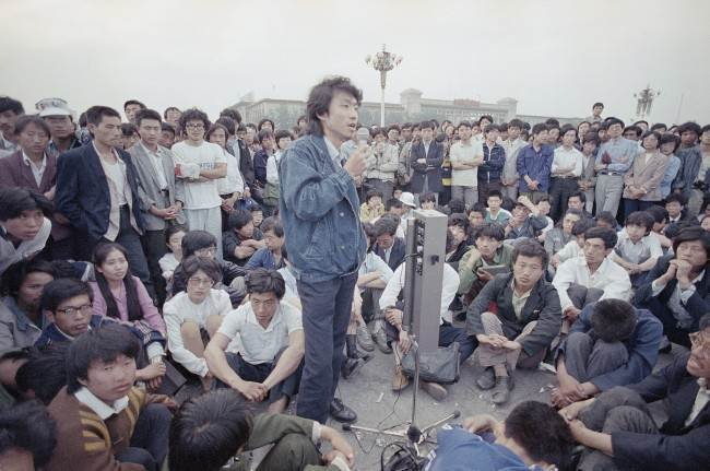 Beijing University students listen as an unidentified strike spokesman details plans for a rally in Tiananmen Square, which they have occupied for the last two weeks, Sunday, May 28, 1989, Beijing, China. (AP Photo/Jeff Widener)