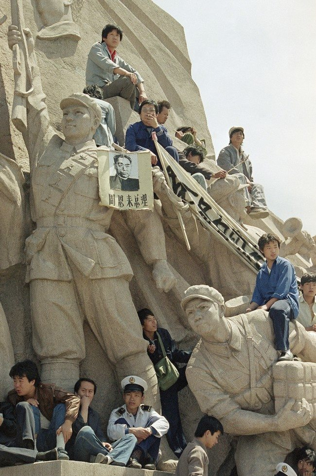 Beijing University students use a monument to the late chairman Mao Tse-Tung at his tomb in Tiananmen Square to press their case for democratic reforms in Beijing, Friday, May 19, 1989. The picture hanging on the statue is the late Premier Chou En-Lai. (AP Photo/Sadayuki Mikami)