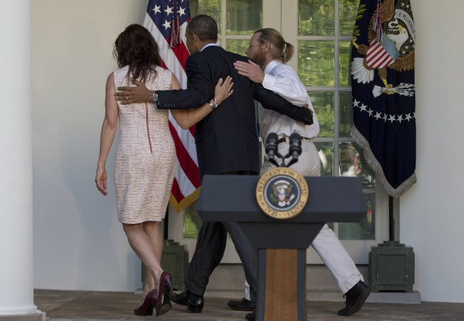 President Barack Obama, center, walks with Jani Bergdahl, left, and Bob Bergdahl, right, to the Oval Office of the White House in Washington, Saturday, May 31, 2014, after speaking about the release of their son, U.S. Army Sgt. Bowe Bergdahl. Bergdahl, 28, had been held prisoner by the Taliban since June 30, 2009. He was handed over to U.S. special forces by the Taliban in exchange for the release of five Afghan detainees held by the United States. (AP Photo/Carolyn Kaster)