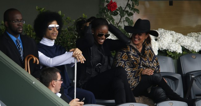 U.S pop singer Prince, second left, and unidentified women, watch Spain's Rafael Nadal playing Serbia's Dusan Lajovic during their fourth round match of the French Open tennis tournament at the Roland Garros stadium, in Paris, France, Monday, June 2, 2014. (AP Photo/Darko Vojinovic)
