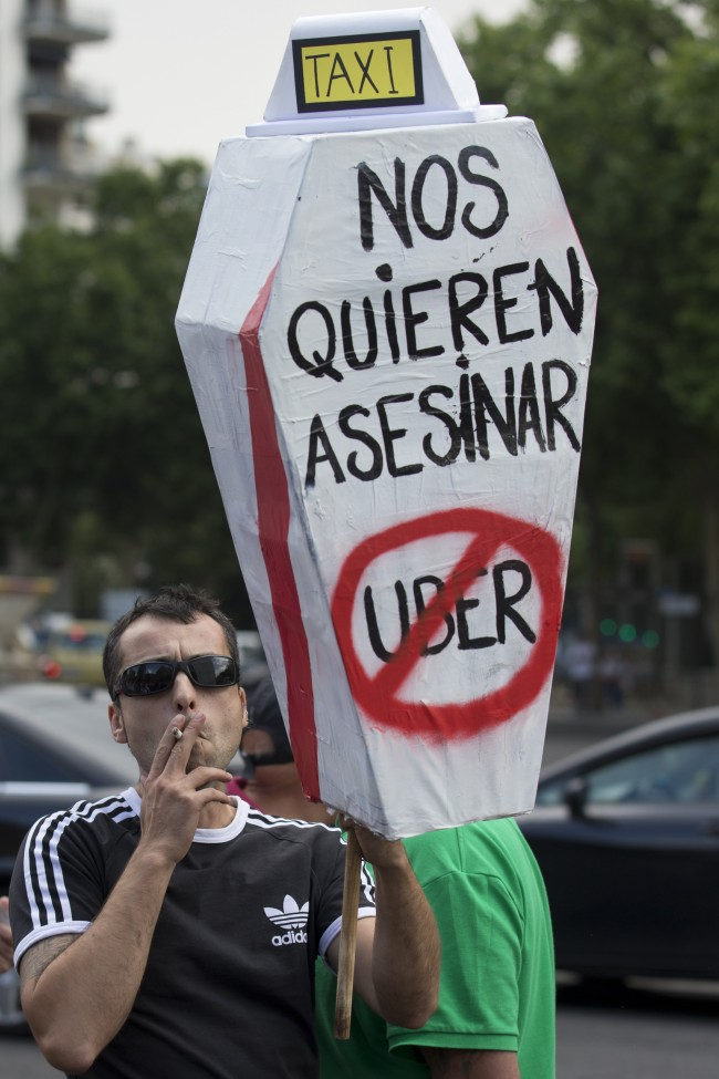 A demonstrator carries a mock coffin with a message reading 'They want to kill us - Uber' during a 24 hour taxi strike and protest in Madrid, Spain, Wednesday, June 11, 2014.