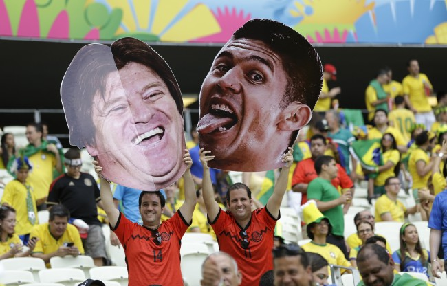 Fans hold photos of Mexico's head coach Miguel Herrera and player Oribe Peralta poor to the group A World Cup soccer match between Brazil and Mexico at the Arena Castelao in Fortaleza, Brazil, Tuesday, June 17, 2014.