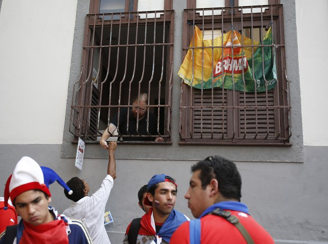 A dealer sells ice-cream through a secured window to soccer supporters beside the Maracana Stadium