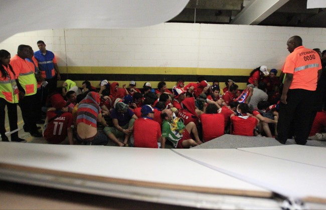 Chile fans sit beside a temporary wall that was torn down