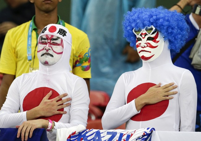 Japanese fans listen to their nation's national anthem before the group C World Cup soccer match between Ivory Coast and Japan at the Arena Pernambuco in Recife