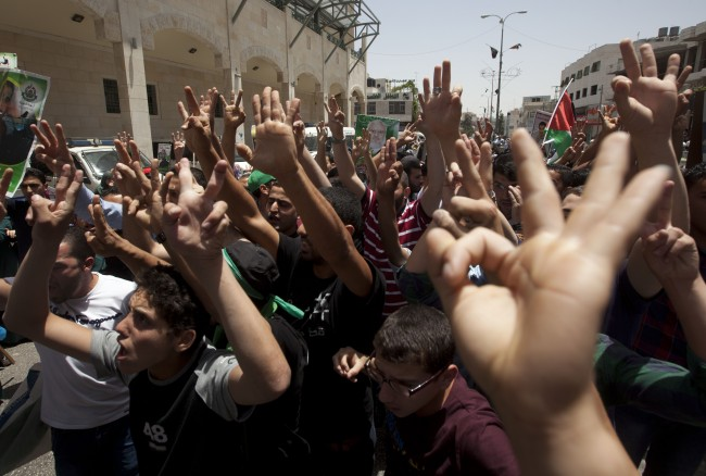 Palestinian supporters of Hamas raise hand gestures including three raised fingers, a sign of their support for the recent abduction of three missing Israeli teens, during a protest against a recent arrest of their comrades by Israeli soldiers, in the West Bank city of Hebron, Friday, June 20, 2014.
