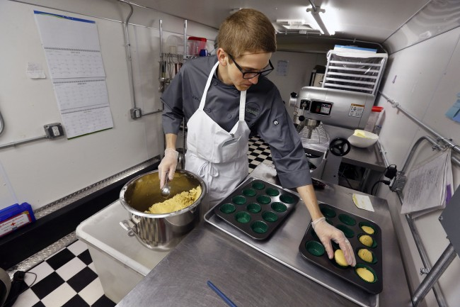 "Chef Alex Tretter prepares a batter for peanut butter and jelly cups, with green cannabis-infused ""canna butter"" in a bowl at left"