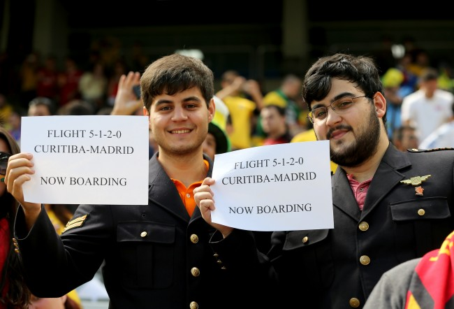 ustralia v Spain - Arena da Baixada Football fans hold up banners that say 'Flight 5-1-2-0 Curitiba - Madrid Now Boarding' in the stands