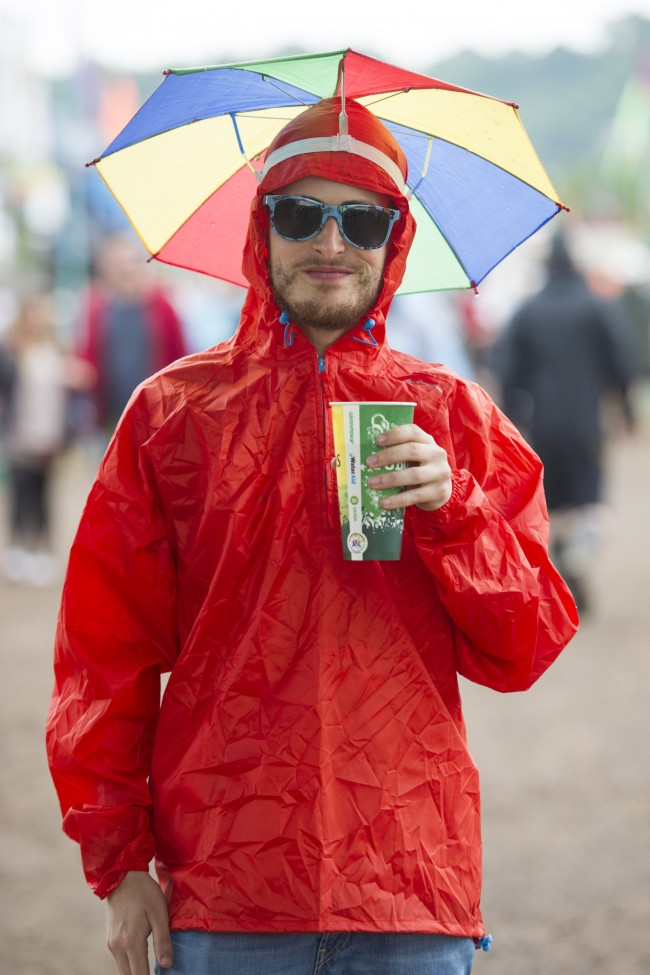 Festival goer Sasa Fratini, from Italy, shelters from the rain