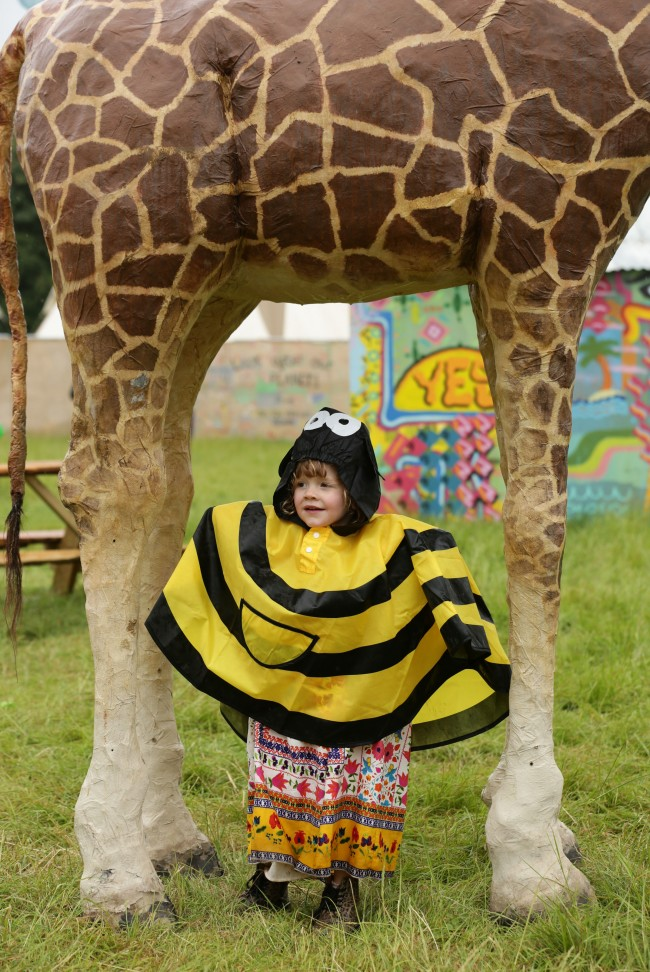 Festivalgoer Willow Rose Kent, aged three, sheltering under a model giraffe