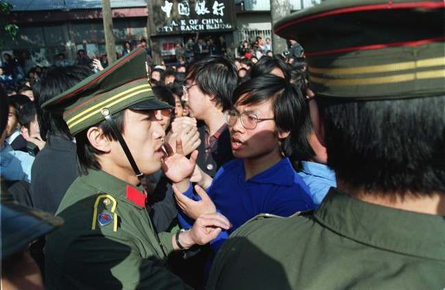 A Beijing University student leader argues with a policeman about the students' right to march as they are told not to march when emerging from their campus. Students from more than forty universities march to Tiananmen Square in protest of the April 26 editorial in the Communist Party newspaper despite warnings of violent suppression.
