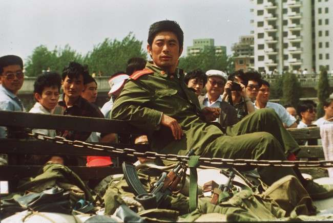 A People's Liberation Army Soldier sits alone with his weapons Sunday after his convoy was stopped by demonstrators seen in the background. (AP Photo/1989)
