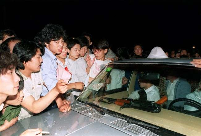 Beijing residents ask soldiers what they were going to do with the machine gun on their dashboard as they surround and stop a carload of chinese soldiers on their way towards to Tiananmen Square in this June 3, 1989 photo. Friday June 4, 1999 is the 10th anniversary of the military assault on pro-democracy protesters who had occupied the square for seven weeks. Hundreds died in the early hours of June 4, 1989 when troops shot their way through Beijing's streets to retake the square. (AP Photo/Mark Avery, File)