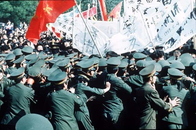 Chinese police try in vain to contain a huge crowd of student marchers during a pro-reform demonstration in Beijing, China, May 4 1989. (AP Photo/S. Mikami)