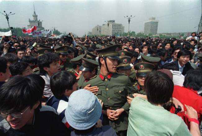 Calling for freedom and democracy, demonstrating students surround policemen near Tiananmen Square in Beijing, China, Thursday afternoon on May 4, 1989. Approximately 100,000 students and workers marched toward the square demanding democratic reforms. (AP Photo/Sadayuki Mikami)