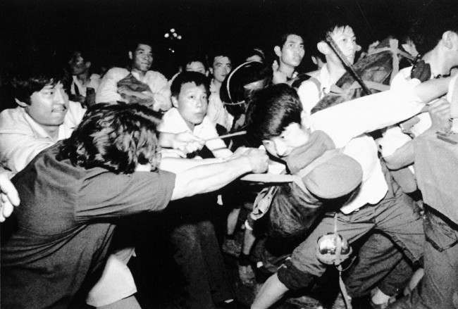 A man tries to pull a Chinese soldier away from his comrades as thousands of Beijing's citizens turned out to block thousands of troops on their way towards Tiananmen Square early Saturday morning, June 3, 1989. (AP Photo/Mark Avery)
