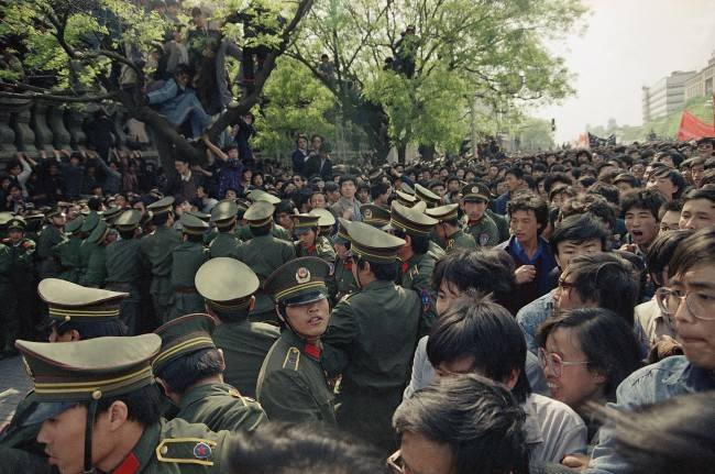 Students demonstrators scuffle with police as they try to break the guard line to march to the Tiananmen Square on Thursday, April 27, 1989 in Beijing. (AP Photo/Sadayuki Mikami)