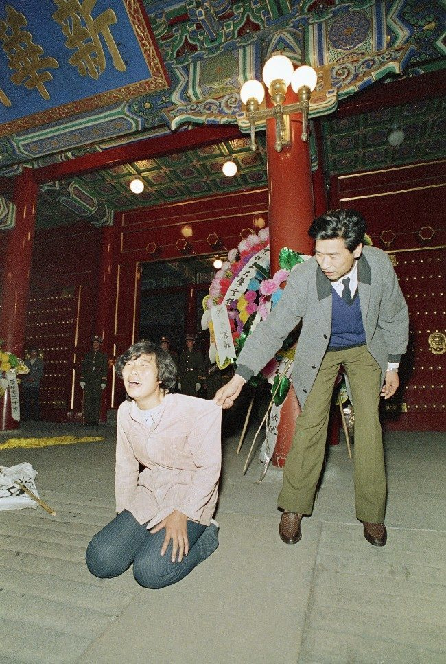A Chinese security guard gently tries to move a weeping young woman away from the ornate entrance to the Chinese Communist Party headquarters, Zhongnanhai, early on Wednesday, April 19, 1989 in Beijing. University students converged on Zhongnanhai after demonstrating in Tiananmen Square all day on Tuesday. The students tried to storm the gate, but were fought back by Chinese security. (AP Photo/Mark Avery)
