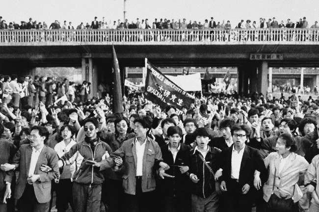 Jubilant student marchers, arms lined, pass under a bridge lined with local supporters, Thursday, April 27, 1989, Beijing, China. Students in the ten of thousands from several Beijing schools demonstrated in defiance of a government ban. (AP Photo/Mark Avery)