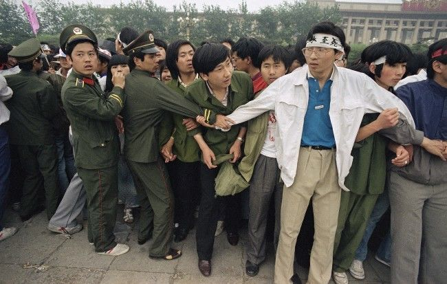 Students and police link area to keep crowd of people, many of the relatives of strikers, from Tiananmen Square, where students have been on hunger strike since Saturday, Thursday, May 18, 1989, Beijing, China. (AP Photo/Sadayuki Mikami)