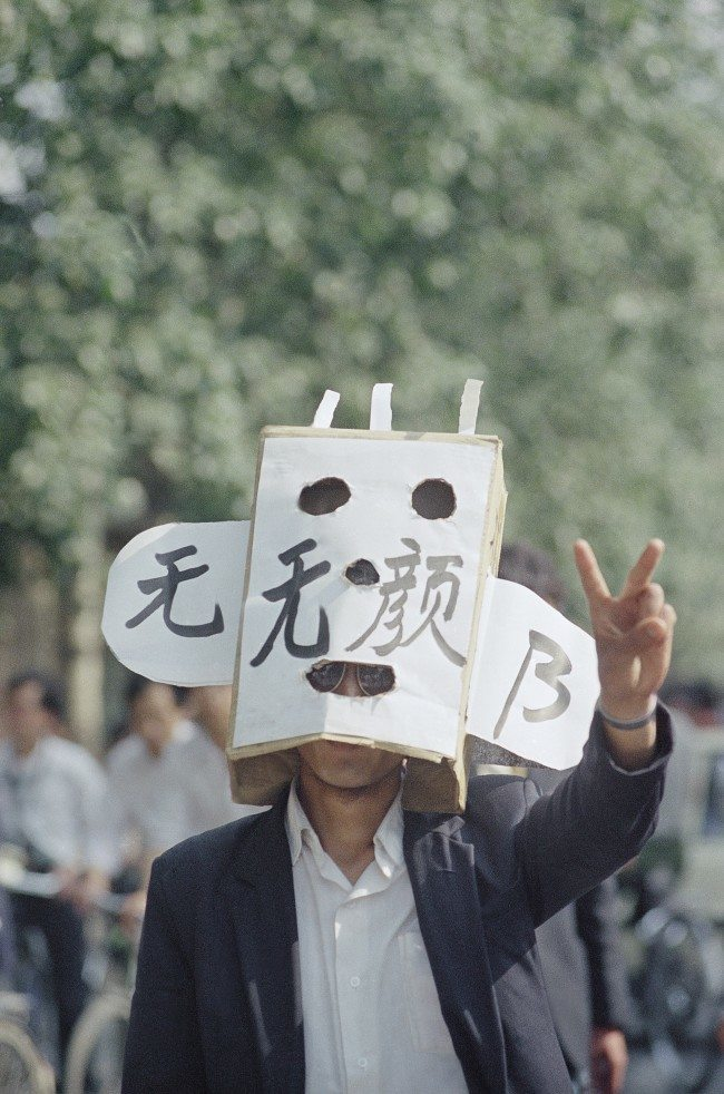 A student protestor flashes a victory sign during a demonstration in Tiananmen Square, Wednesday, May 17, 1989, Beijing, China. The characters on his mask mean losing face. (AP Photo/Mark Avery)