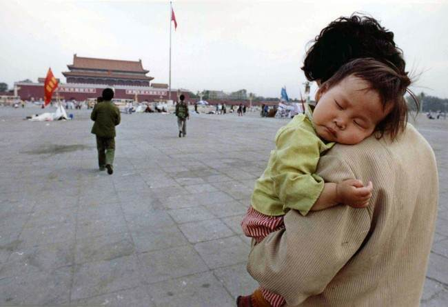 A child sleeps on his mother's shoulder as she crosses Tiananmen Square, Beijing, on May 29, 1989. Many students have tired and returned to their classes following three weeks of pro-democratic rallies. (AP Photo/Staff/Widener)