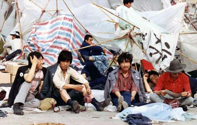 A group of students rest before their tattered tents in Tiananmen Square, Beijing, on May 27, 1989, where thousands of students continue their sit-in protest to press the government for political reforms. (AP Photo/Staff/Widener)