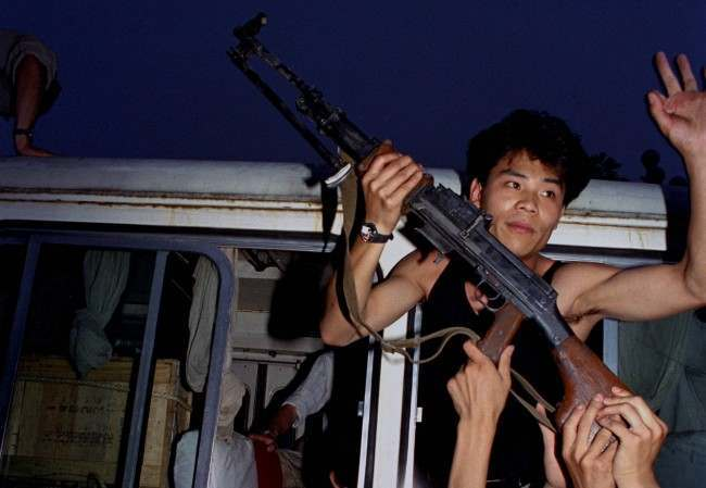 An anti-government protester in Beijing holds a rifle in a bus window, June 3, 1989. Pro-democracy protesters had been occupying Tiananmen Square for weeks; hundreds died that night and the following morning in clashes with Chinese troops. (AP Photo/Jeff Widener)