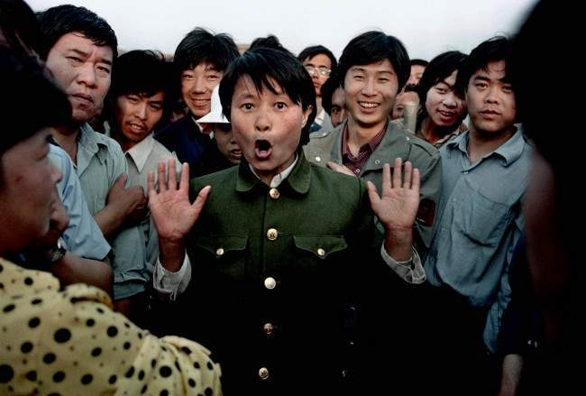 A woman soldier sings among pro-democracy protesters occupying Beijing's Tiananmen Square, about June 2, 1989. Police and military would occasionally mix with protesters in an attempt to keep the demonstration peaceful. In the early morning hours of June 4, 1989, soldiers overran the square, leaving hundreds dead overnight. (AP Photo/Jeff Widener)