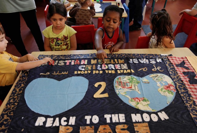 Israeli Jewish Muslim and Christian children sit around a banner that they helped make which will be taken into space, at the YMCA Peace Preschool in Jerusalem, Wednesday, June 17, 2009. The banner will be blasting off with NASA's space shuttle on its next mission to the International Space Station in November 2009.(AP Photo/Tara Todras-Whitehill)