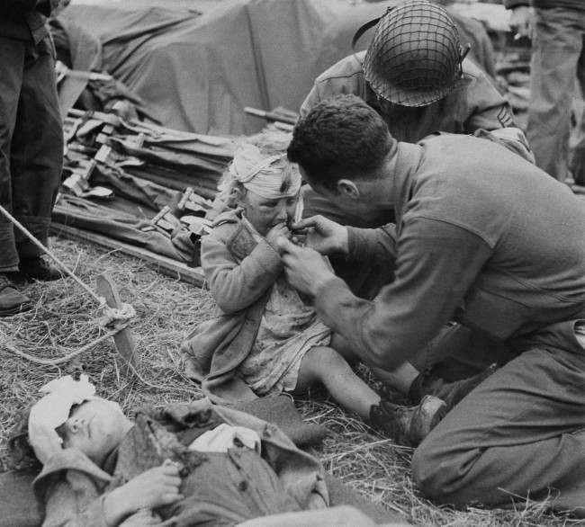 American Army medical corpsmen try to assuage the grief of a little French girl with a gift of candy in France, June 17, 1944. Her head is bandaged and face swollen. Another child lies in front with his head bandaged. Both youngsters are evidently under the effects of the terror of Normandy. (AP Photo)