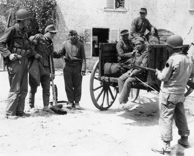 An American soldier and a French peasant assist a wounded Nazi prisoner into a cart in which he and others captured in a small French village, in Normandy, on June 10, 1944, were transported back to the beach en route to England and internment. (AP Photo)