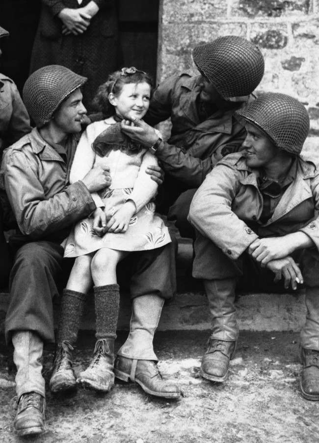 A little French girl finds three admirers from the ranks of American forces who have made a speedy and successful advance through Normandy, France on June 22, 1944. From left to right,Private Robert D. Furra, Private Willie Johnson and Private C.K. Jones. (AP Photo)