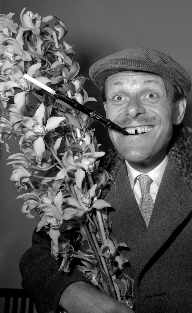 TV's elegant comedian Terry-Thomas, who exhibits a distinctive sartorial style, returns from a holiday in Madeira sporting a cap and extended cigarette holder. He carries a bush of orchids for his wife. PA/PA Archive/Press Association Images