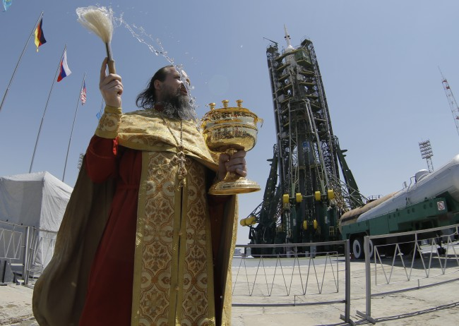 An Orthodox priest conducts a blessing service in front of the Soyuz TMA-13M spacecraft at the Russian leased Baikonur cosmodrome, Kazakhstan, Tuesday, May 27, 2014. The Soyuz is scheduled to launch Thursday, May 29. (AP Photo/Dmitry Lovetsky)