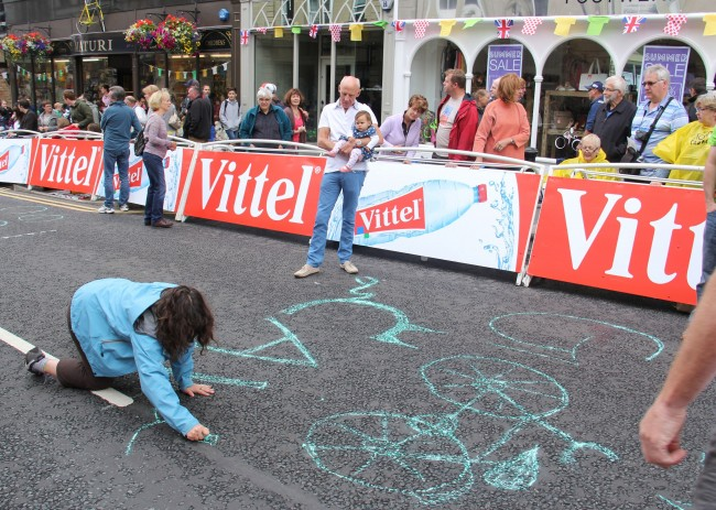 A fan of rider Mark Cavendish writes his name in chalk near the finish line in Harrogate during stage one of the 2014 Tour De France.