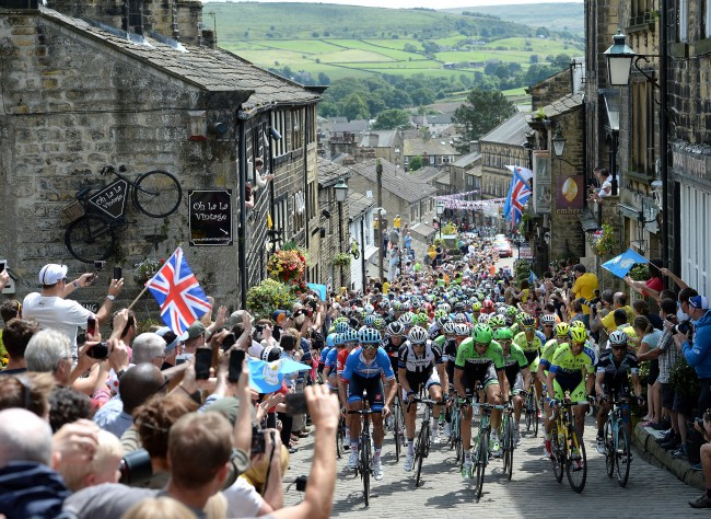 The peloton rides up Main Street as stage two of the Tour de France passes through Haworth, Yorkshire.