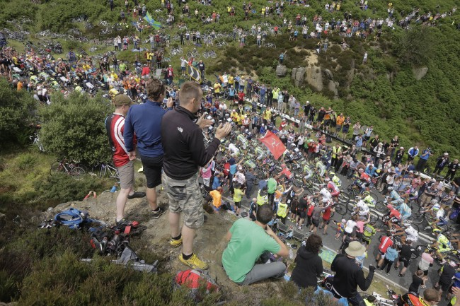 Spectators line the road as the pack climbs Blubberhouses pass during the second stage of the Tour de France cycling race over 201 kilometers (124.9 miles) with start in York and finish in Sheffield, England, Sunday, July 6, 2014. (AP Photo/Laurent Cipriani)