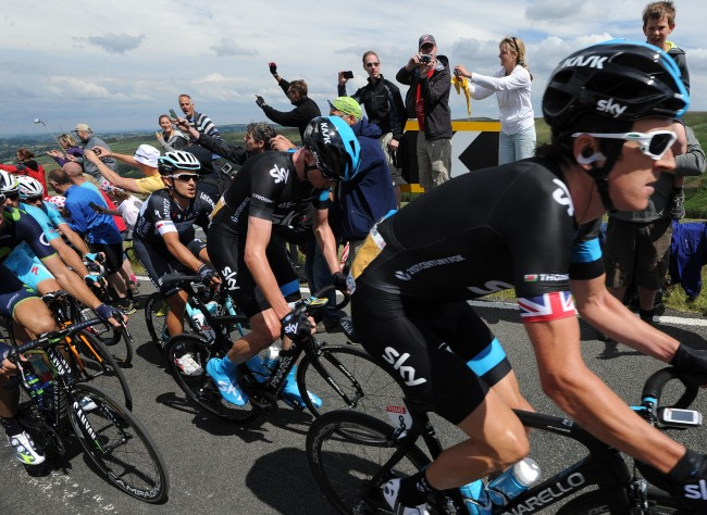 Team Sky's Chris Froome is protected by his teammates as they are cheered along stage two of the Tour de France passes over Holme Moss Moor, Yorkshire.