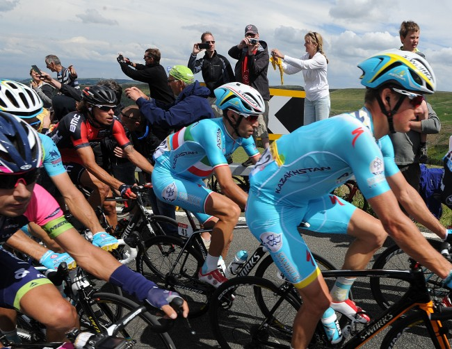 Astana Pro Team's Vincenzo Nibali (centre) sits inside the peloton as stage two of the Tour de France passes over Holme Moss Moor, Yorkshire.