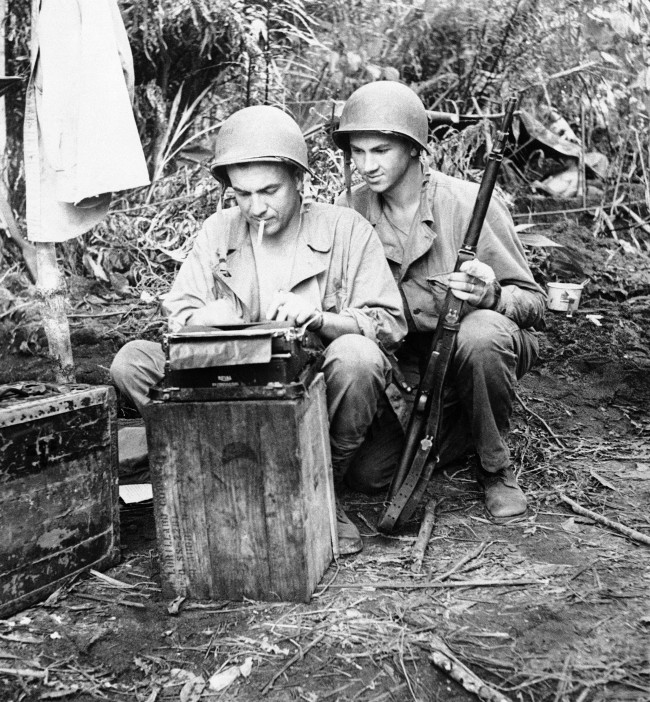 Mst. Sgt. John A. Kutcher of Portland, Ore., (right) looks on as Associated Press correspondent William F. Boni of New York works at his typewriter somewhere in New Guinea on August 5, 1943. Boni was awarded the Purple Heart decoration in recognition of wounds received on July 9 when the barge on which he was a passenger was strafed by machine guns and cannons off Nassau bay on the New Guinea coast. (AP Photo) Ref #: PA.11506402  Date: 05/08/1943