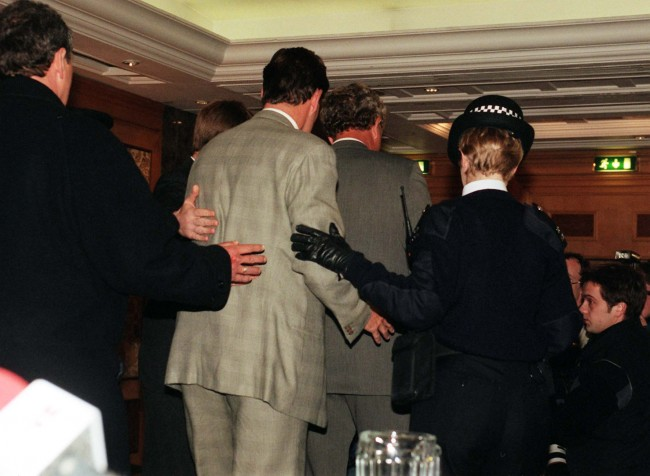 Glenn Hoddle is escorted off the stage after speaking at a news conference at the Lancaster Park Hotel in London after the announcement that his contract as manager of the England football team has been terminated.  Ref #: PA.1161411  Date: 02/02/1999