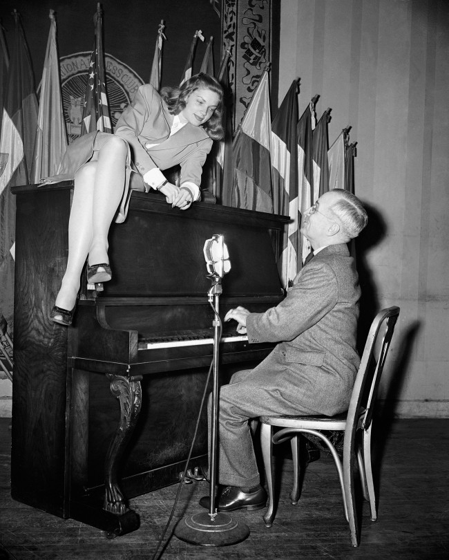In this Feb. 10, 1945 file photo, Vice President Harry S. Truman plays the piano as new movie star Lauren Bacall lies on top of it during her appearance at the National Press Club canteen in Washington. Through the years, commanders-in-chief have turned musicians-in-chief, with varying results. (AP Photo)