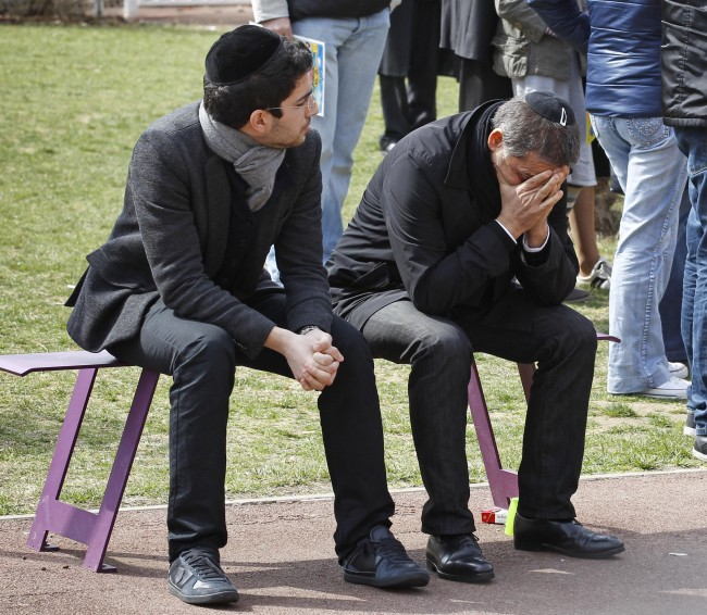 A man is overcome by emotion during a ceremony for the shooting victims at the Ozar Hatorah Jewish school where a gunman opened fire Monday killing four people in Toulouse, southwestern France, Tuesday, March 20, 2012. Police blanketed southern France on Tuesday, searching for a gunman _ possibly a racist, anti-Semitic serial killer _ who killed four people at a Jewish school and may have filmed his attack.(AP Photo/Remy de la Mauviniere)