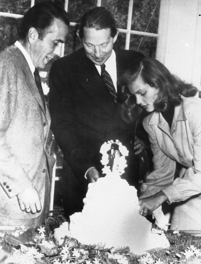 In this May 21, 1945 file photo, novelist Louis Bromfield, center, helps actor Humphrey Bogart and his bride, actress Lauren Bacall, cut the cake after their wedding at Bromfield's Malabar Farm near Lucas, Ohio.