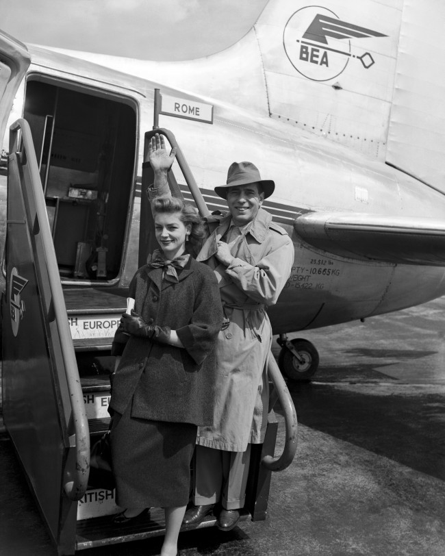 American actors Humphrey Bogart and his wife Lauren Bacall, board a BEA Viking for Rome at Heathrow Airport. 1951.