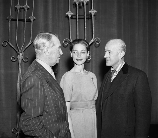 Maurice Chevalier (left) talks to Lauren Bacall and Alec Guinness at the rehearsal for the Royal Film Performance at the Empire Theatre in Leicester Square, London. Date: 01/02/1959